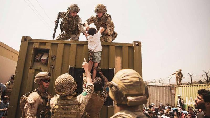 UK coalition forces, Turkish coalition forces, and U.S. Marines assist a child during an evacuation at Hamid Karzai International Airport, Kabul, Afghanistan, Aug. 20, 2021.